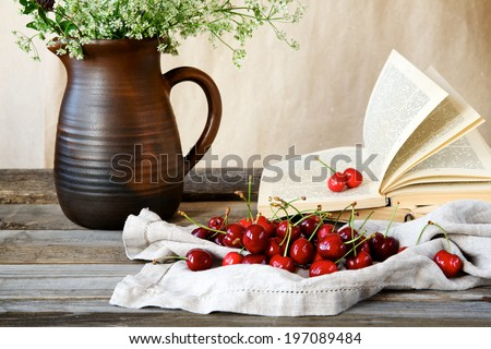 Cherry on a background of old books and wildflowers. - stock photo