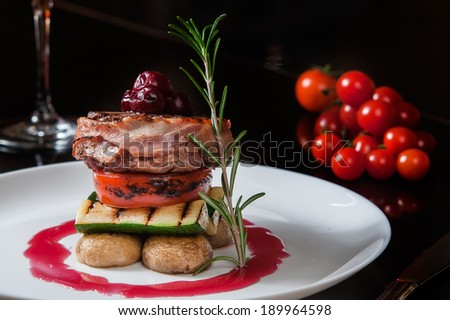 Cherry on a meat steak. Grilled meat grilled pork with vegetables on grill tomatoes with avocado and grilled champignons lies on a plate with a glass of red wine and a sprig of rosemary to the menu - stock photo