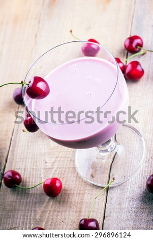 Cherry smoothie with ripe cherries on the table - stock photo