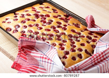 Cherry sponge cake after baking in tin with towel - stock photo