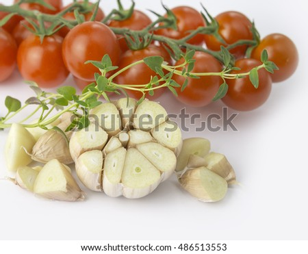Cherry tomato with garlic and fresh thyme on white background