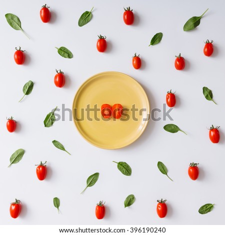 Cherry tomatoes and basil leaves pattern on white background. Flat lay. - stock photo