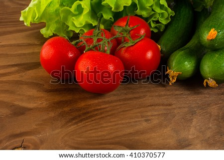 Cherry tomatoes and cucumber on wooden table. Tomato.  Cucumber.  Ripe vegetables. Fresh vegetables. Cherry tomato. Healthy eating