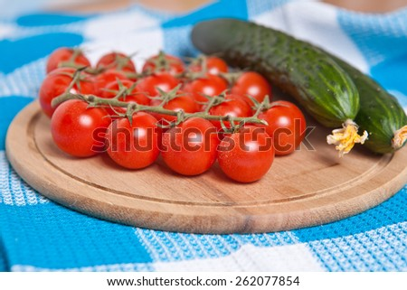 cherry tomatoes and cucumbers on the cutting board close up