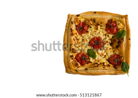 Cherry tomatoes and feta cheese tart made with butter puff pastry. Isolated on white, top view.