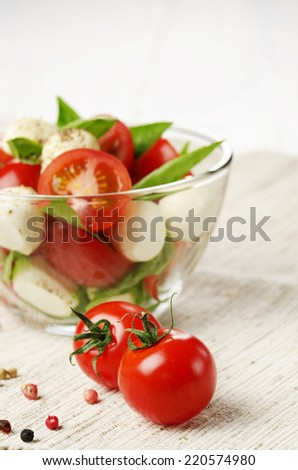 Cherry tomatoes and Homemade Caprese salad in glass bowl - stock photo