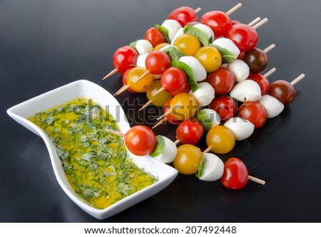 Cherry tomatoes and mozzarella on skewers and a vinaigrette sauce with basil, on a black background - stock photo