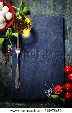 Cherry tomatoes, basil leaves, mozzarella cheese and olive oil for caprese salad. Lots of copy space - stock photo
