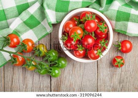 Cherry tomatoes bowl on wooden table. Top view - stock photo