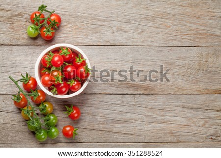 Cherry tomatoes bowl on wooden table. Top view with copy space - stock photo