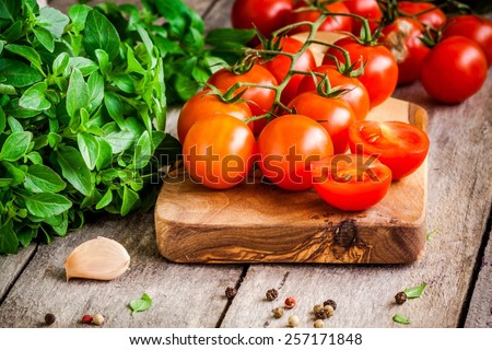 cherry tomatoes, fresh organic basil with garlic and peppers in olive cutting board - stock photo