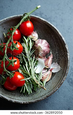 Cherry tomatoes, garlic and rosemary in a ceramic bowl - stock photo