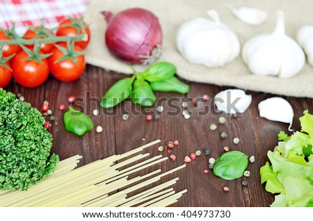Cherry tomatoes, garlic, spaghetti, parsley and salad on wooden table