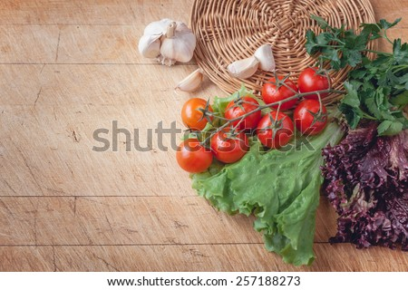 cherry tomatoes , green salad and garlic on a wooden cutting board with space for writing