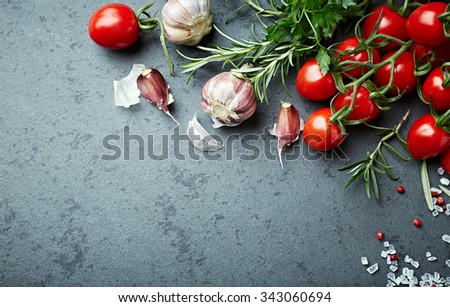 Cherry tomatoes, herbs and spices on  a stone background - stock photo