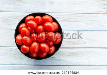 cherry tomatoes in a black bowl on aged wooden table - stock photo