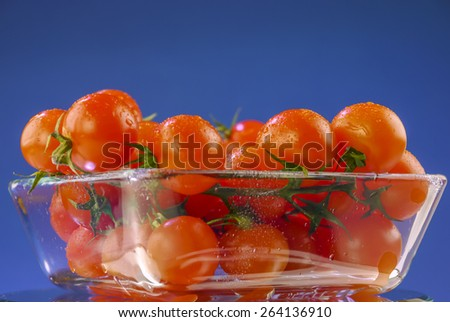 Cherry tomatoes in a glass bowl on blue background - stock photo