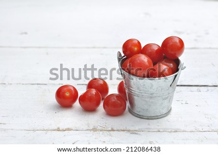 cherry tomatoes in a small metal pot on white wood - stock photo