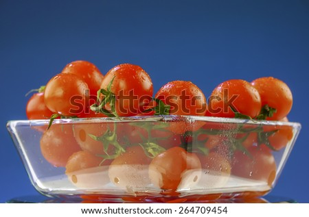 Cherry tomatoes in a transparent bowl on blue background - stock photo