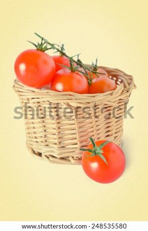 cherry tomatoes in a wicker basket on a white background. picture in retro style - stock photo