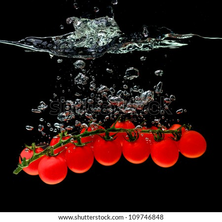 cherry tomatoes in the water on black background - stock photo