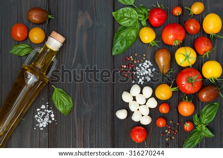 Cherry tomatoes of various color, mozzarella, basil leaves, spices and olive oil from above over dark wooden table. Italian caprese salad recipe ingredients. Top view, free text copy space - stock photo