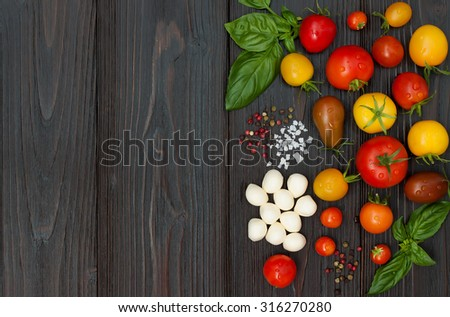 Cherry tomatoes of various color, mozzarella, basil leaves, spices from above over dark wooden table. Italian caprese salad recipe ingredients. Top view, free text copy space - stock photo