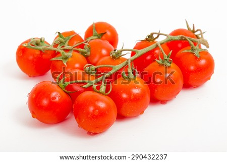 Cherry tomatoes on a branch on a white background