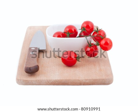 cherry tomatoes on a wooden board with a knife on a white background - stock photo