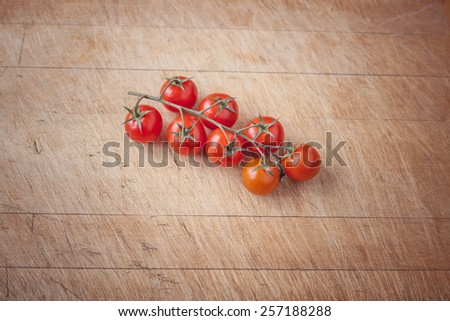cherry tomatoes on a wooden cutting board with space for writing