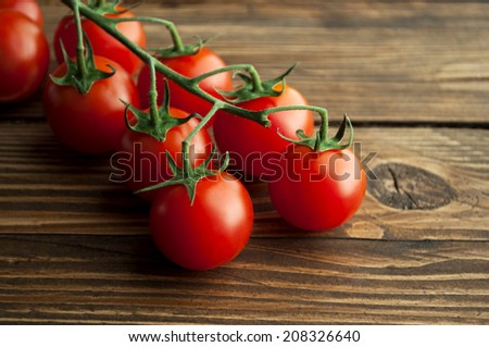 cherry tomatoes on a wooden surface with natural light - stock photo