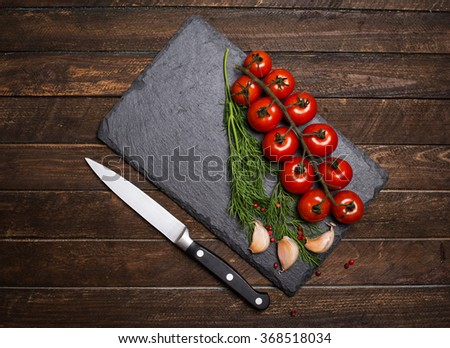 Cherry tomatoes on the vine with garlic pepper and dill on black slate stone. Top view. Vegetarian food, health or cooking concept. - stock photo