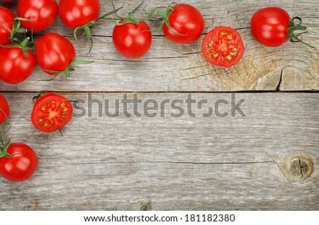 Cherry tomatoes on wooden table background with copy space - stock photo
