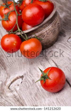 Cherry tomatoes on wooden table with water drops