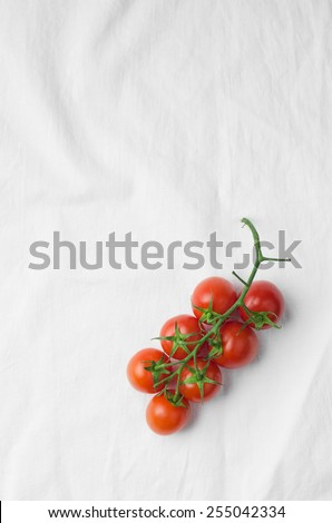 Cherry tomatoes over white cloth, above view with lots of copy space - stock photo