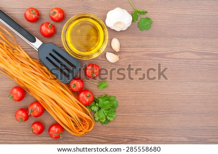 Cherry tomatoes, pasta, olive oil, garlic, herbs and pasta tongs on the old wooden background. Rustic style. Traditional Italian food. Selective focus - stock photo