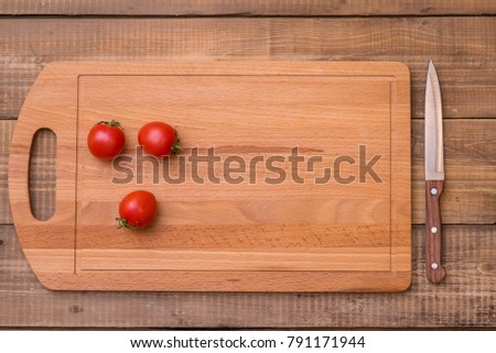 Cherry tomatoes prepared for cutting on wooden board. Place for text. Recipe design horizontal. Top view