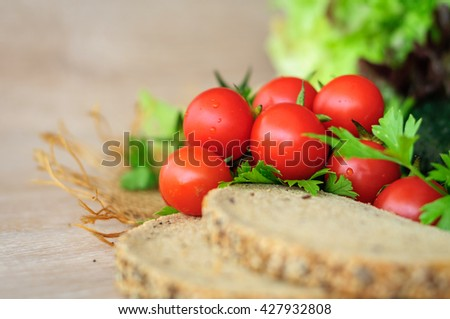 cherry tomatoes, slices of black bread with sunflower seeds, parsley and cucumber on the table