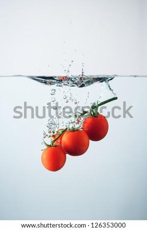 Cherry tomatoes splash. Studio shot - stock photo