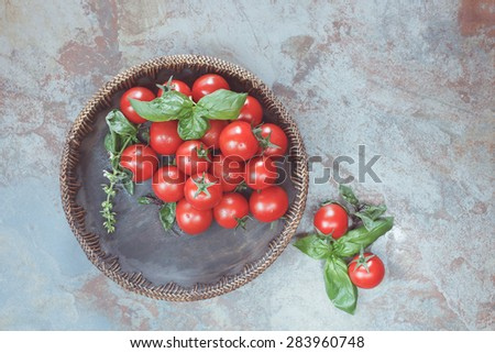 Cherry tomatoes. Tomatoes in a wooden bowl on rustic table.  Overhead view with retro style processing. Natural light - stock photo