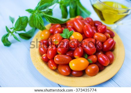Cherry tomatoes with basil and olive oil on wooden background close-up.