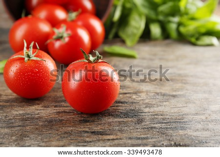 Cherry tomatoes with basil on wooden table close up - stock photo