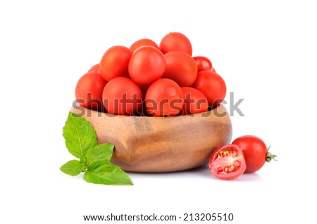 Cherry tomatoes with green basil leaves in bamboo plate on white background - stock photo