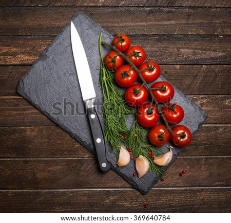 Cherry tomatoes with knife garlic pepper and dill on black slate stone. Top view. Vegetarian food, health or cooking concept. - stock photo