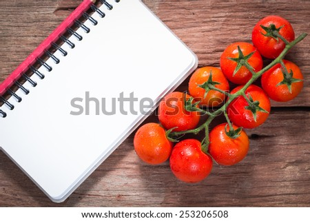 Cherry tomatoes with notepaper on wood