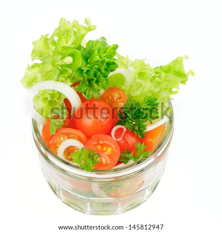 Cherry tomatoes with onions and salad in glass on white background