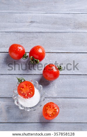 Cherry tomatoes with salt on a wooden background. Selective focus. - stock photo