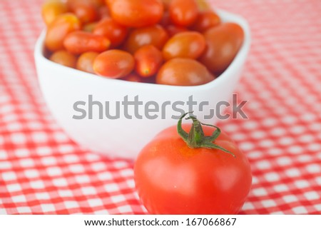cherry tomatos and tomatos in bowl on checkered fabric
