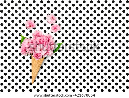 Cherry tree flowers in ice cream waffle cone on polka dot background. Flat lay. Minimal concept - stock photo