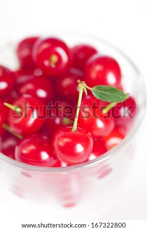 cherry with green leaf and a cup of cherries on a white background
